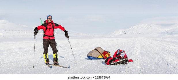 young man with ski during winter expedition in wilderness mountainous landscape - panoramic view