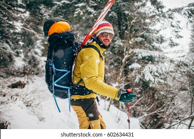 Young man with ski standing in the snow forest