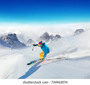 Young man skier running down the slope in Alpine mountains. Winter sport and recreation, leisure outdoor activities.