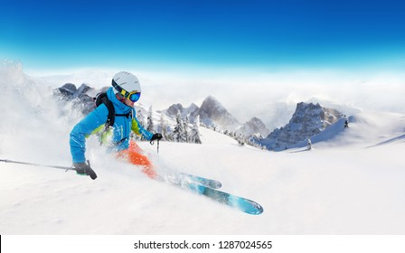 Young man skiing on piste. Winter sport and recreation in alpen mountain.