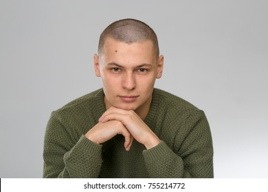 A young man is skinhead in a green military style sweater. studio
