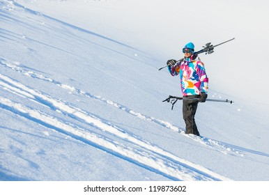 Young man with skis and a ski outfit walking in snow at winter outdoor in the Zillertal Arena, Austria