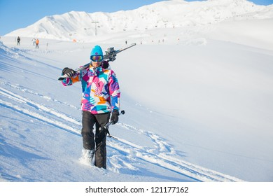Young man with skis and a ski outfit walking in snow at winter outdoor. Tirol, Austria