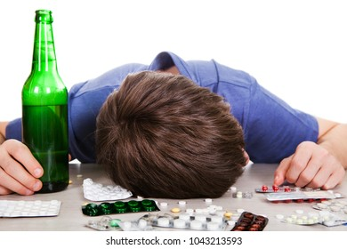 Young Man sleep with a Pills and Bottle of the Beer on the Table