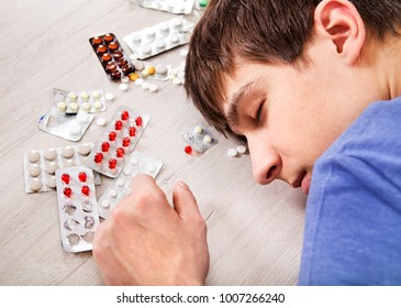 Young Man sleep with a Pills on the Table