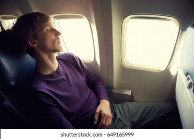young man sleeping in an airplane seat. traveler in an plane
