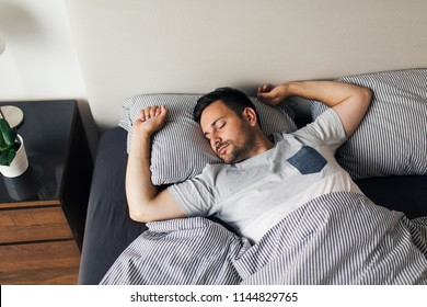 Young man sleeping alone on his back