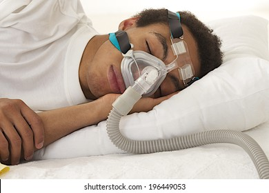 young man  sleeping with apnea and CPAP machine