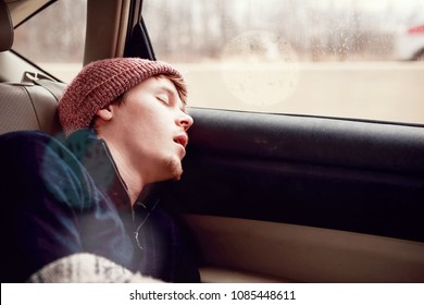 Young man sleeping in the backseat of a car on a trip