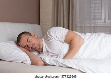 Young man sleeping in a bed