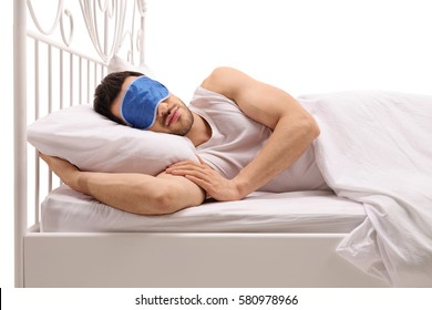 Young man sleeping in bed with an eye mask isolated on white background