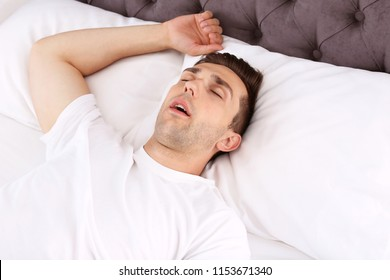 Young man sleeping in bed at home