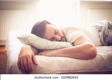 Young man sleeping in bed. Space for copy. Close up.