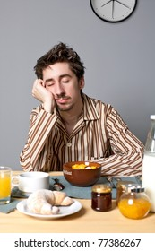 Young man sleeping at breakfast table