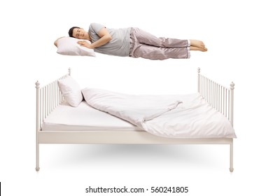 Young man sleeping and floating above a bed isolated on white background
