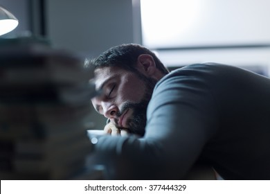 Young man sleeping at his desk late at night, stress and exhaustion concept