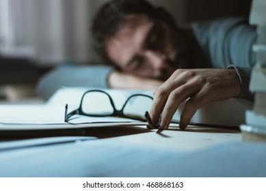 Young man sleeping at his desk late at night, he is leaning on a book and holding glasses, stress and exhaustion concept