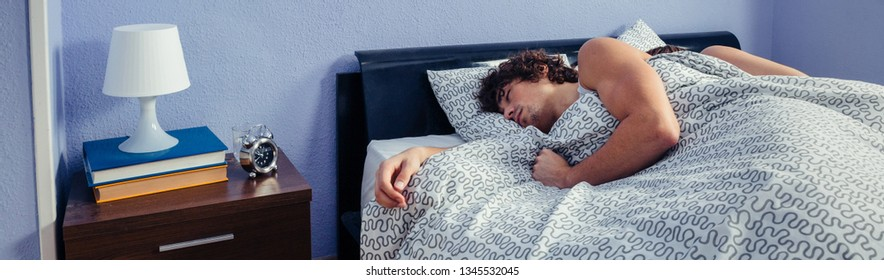 Young man sleeping with his wife on their backs in bed