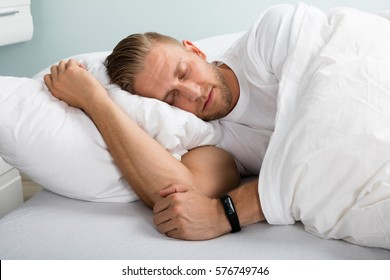 Young Man Sleeping On Bed With Eyes Closed