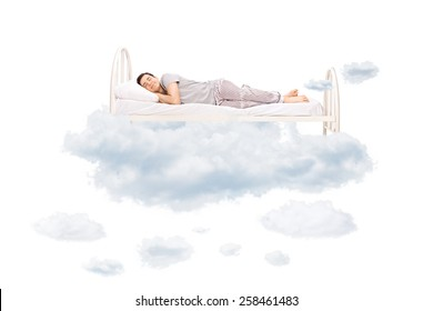 Young man sleeping on a comfortable bed in clouds isolated on white background