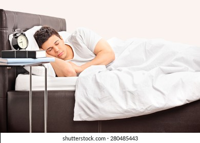 Young man sleeping on a comfortable bed covered with a white blanket in a bedroom
