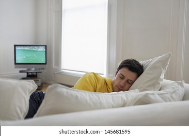 Young man sleeping on couch with television in background