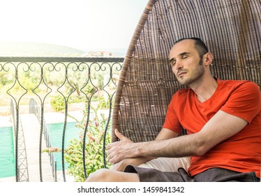 Young man sleeping on a swinging chair in a balcony on a hot sunny day. Travel and relaxing concept.