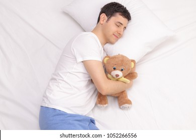 Young man sleeping with a teddy bear