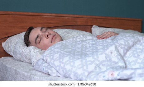 A young man is sleeping under the covers. A man lies in bed in his room.