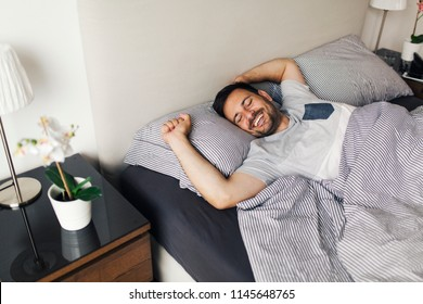 Young man sleeping waking up and stretching in his bed