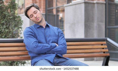 Young Man Sleeping while Sitting Outdoor on Bench
