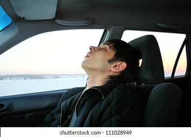 young man sleeps in passenger compartment of the car