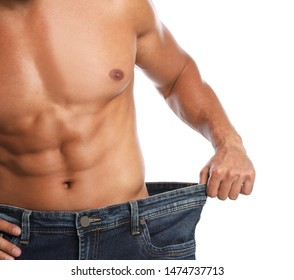 Young man with slim body in old big size jeans on white background, closeup view