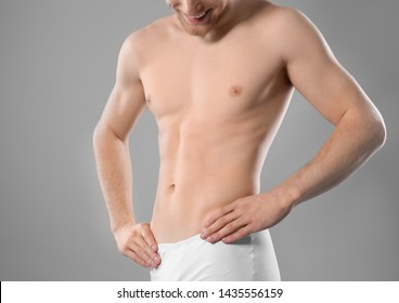 Young man with slim body on grey background, closeup