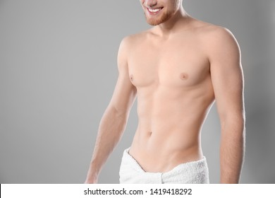 Young man with slim body in towel on grey background, closeup. Space for text