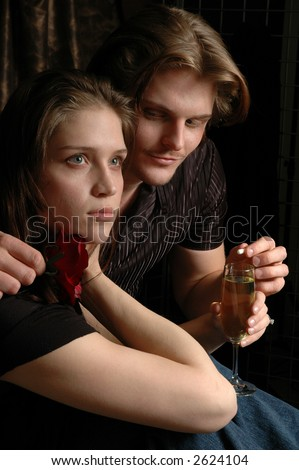 A young man slipping a date rape pill in a woman's drink while she is looking away