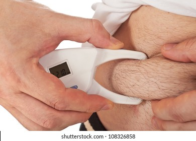Young man with small amount of fat measuring his body fat with the caliper
