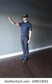 Young man in smart glasses headset showing how to work with virtual reality using special gestures