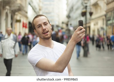 Young Man with smartphone walking cross city