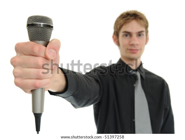 Young man smiles and holds up microphone on white