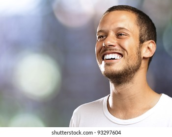young man smiling with a blurred city as a background