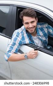 Young man smiling at camera showing key in his car