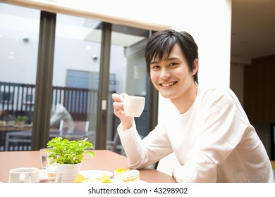 A young man smiling and having coffee