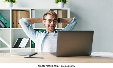 Young man smiling as he reads the screen of a laptop computer while relaxing working on a comfortable place by the wooden table at home. Happy Social distancing - Shutterstock ID 1676569027