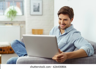 Young man smiling as he reads the screen of a laptop computer while relaxing on a comfortable couch at home in his jeans