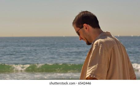 Young Man Smiling as He Walks Along the Beach