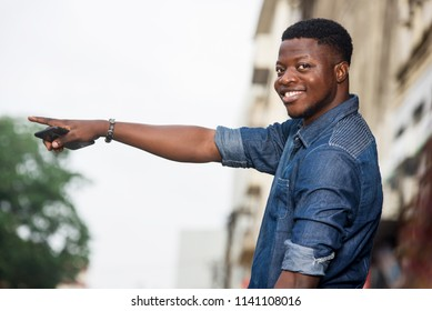 Young man smiling with his hand raised, holding a mobile phone and standing in the street waiting for taxi.