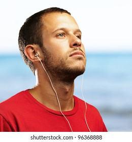 young man smiling and listening to music with a sea as a background