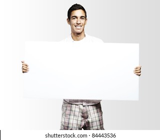 young man smiling and showing a big banner against a grey background