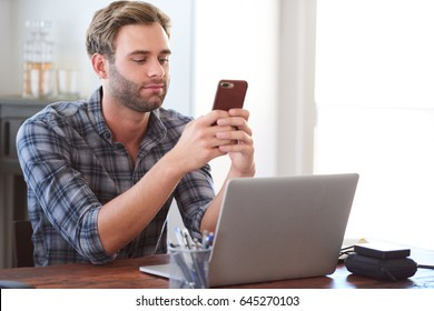 Young man smiling slightly as he flirts via text message on his phone while seated at his desk behind his laptop, procrastinating for as long as possible before getting back to work.